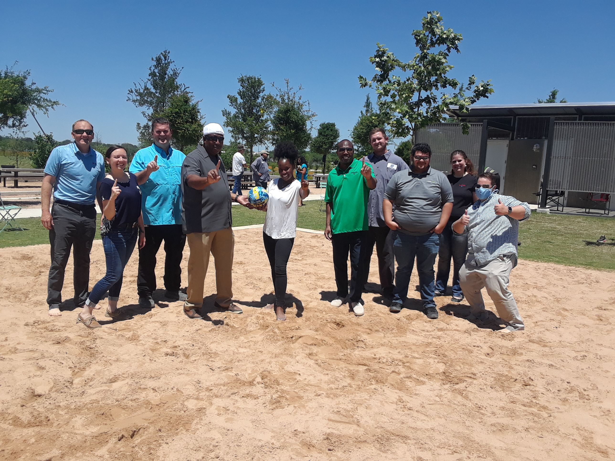 City of Buda employees celebrate after a sand volleyball game